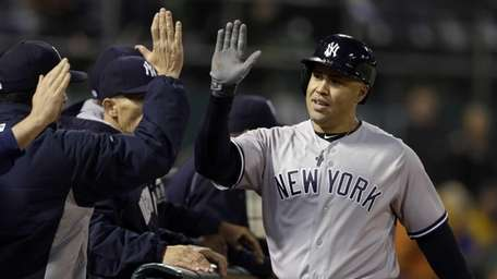 New York Yankees' Carlos Beltran is congratulated after