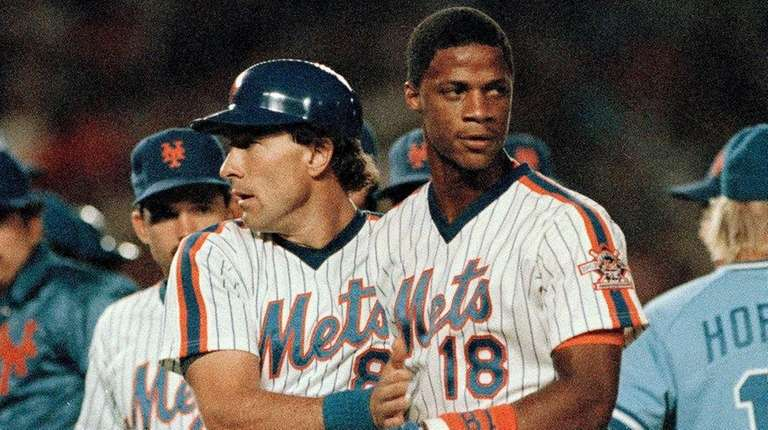 Mets catcher Gary Carter, left, escorts teammate Darryl