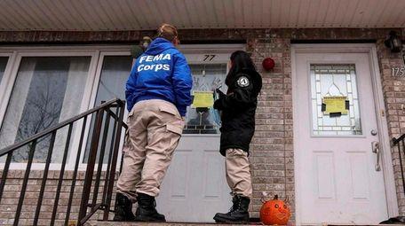 Workers from FEMA go door-to-door on Nov. 13,