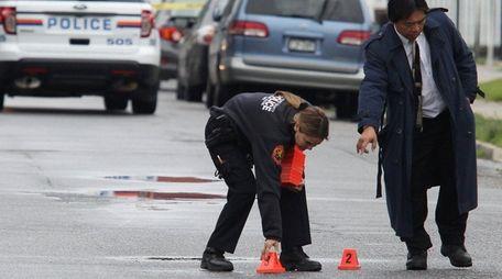 Nassau police investigate the scene where two men