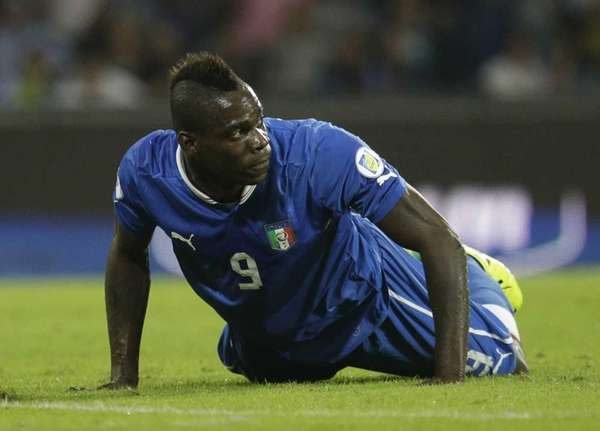 Italy's Mario Balotelli lies on the pitch during