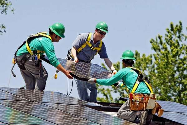 SolarCity employees install a solar panel on a