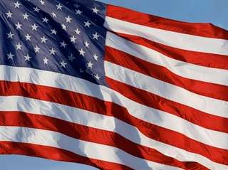 Above, an American flag waves over an auto
