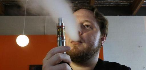 Bruce Schillin, 32, exhales vapor from an e-cigarette