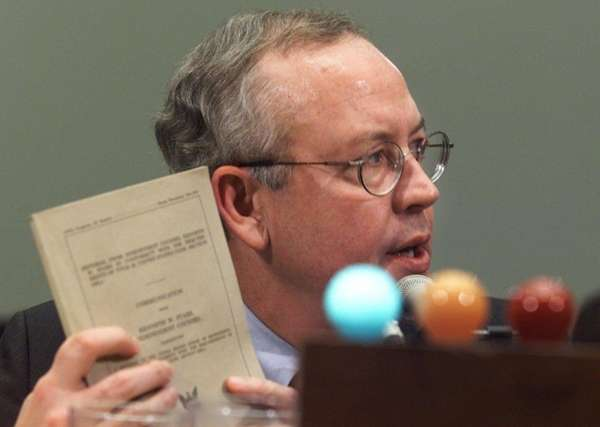 Independent Counsel Kenneth Starr holds up his report