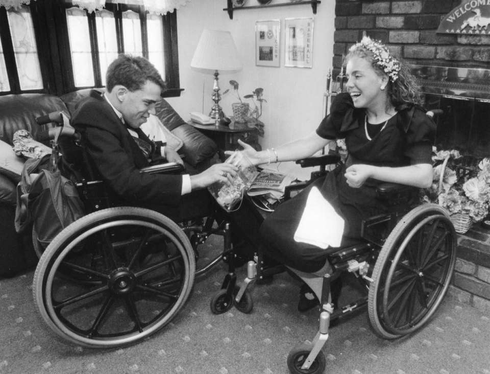 Charlie Stoltz exchanges flowers with his prom date,