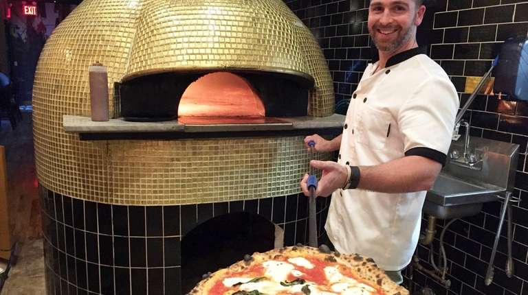 Michael Vigliotti takes a Margherita pizza out of