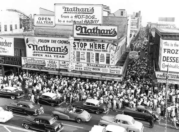 Huge crowds gather on the sidewalk surrounding Nathan's
