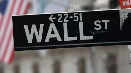 A street sign for Wall Street hangs outside