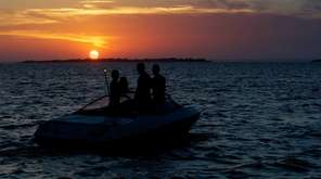 A trio enjoys a sunset view while boating
