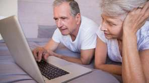 Retired couple using together laptop on bed in