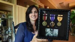 Lisa Hogan holds her uncle's Purple Heart medal
