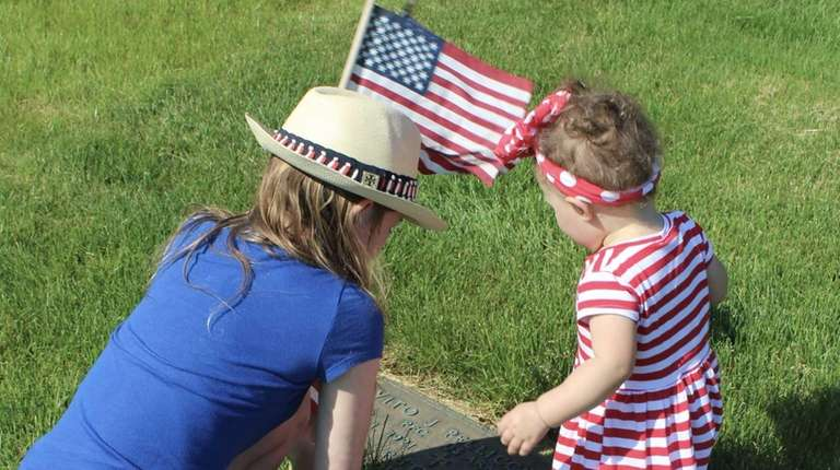 Jocelyn, 12, and Michaela, 16 months, placing flags
