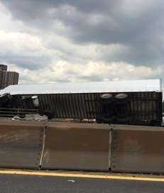 A tractor-trailer hangs over the Sheridan Parkway after