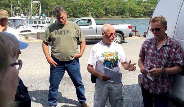 Riverhead fisherman Phil Karlin, center in white, discusses