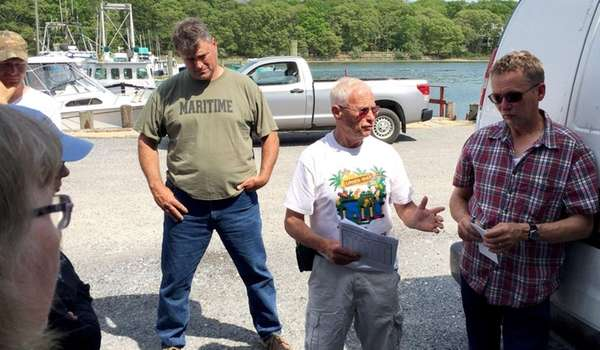 Riverhead fisherman Phil Karlin, center in white, discusses
