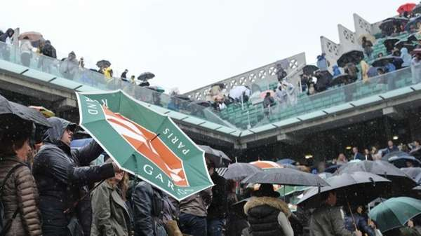 Spectators shield themselves from the rain as the