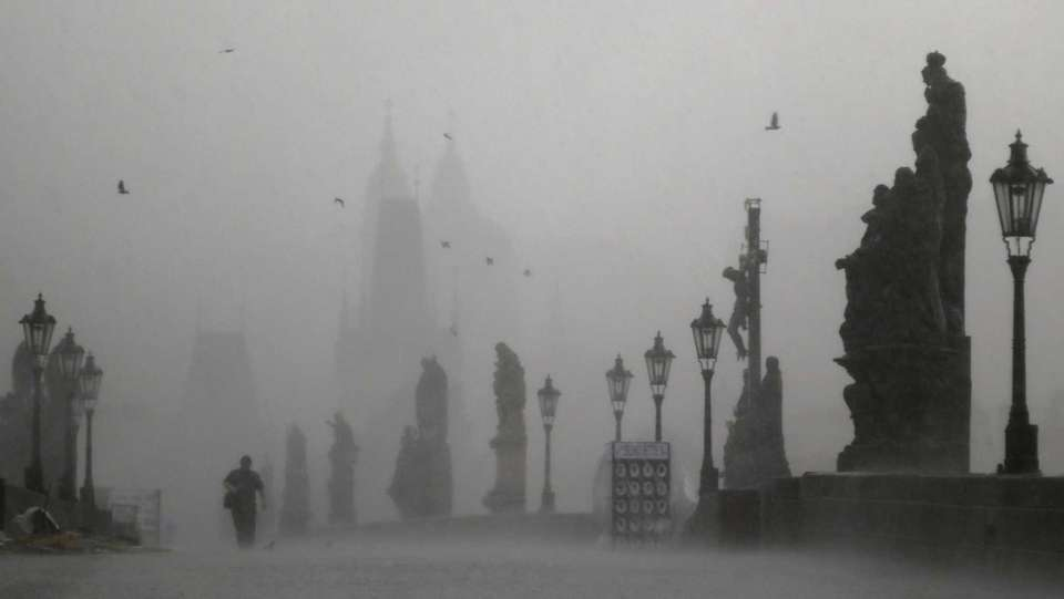 A man crosses the medieval Charles Bridge during