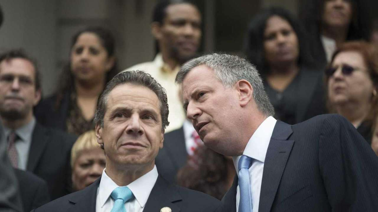 Gov. Andrew Cuomo listens to Mayor Bill de