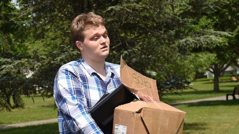Chris Snyder, 22, of Shirley, carries his belongings