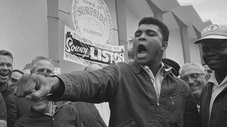 Cassius Clay, young heavyweight fighter, thrusts his fist