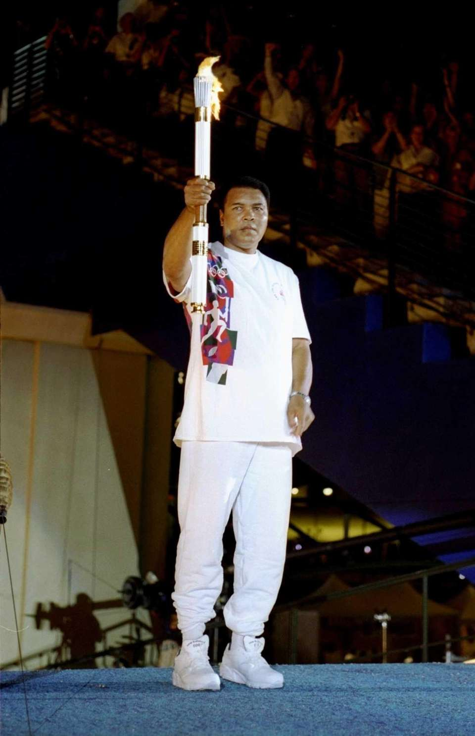 Muhammad Ali holds the torch before lighting the