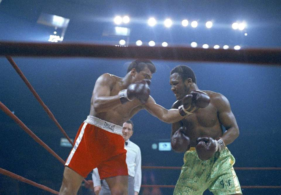 Muhammad Ali, red trunks, and Joe Frazier, green