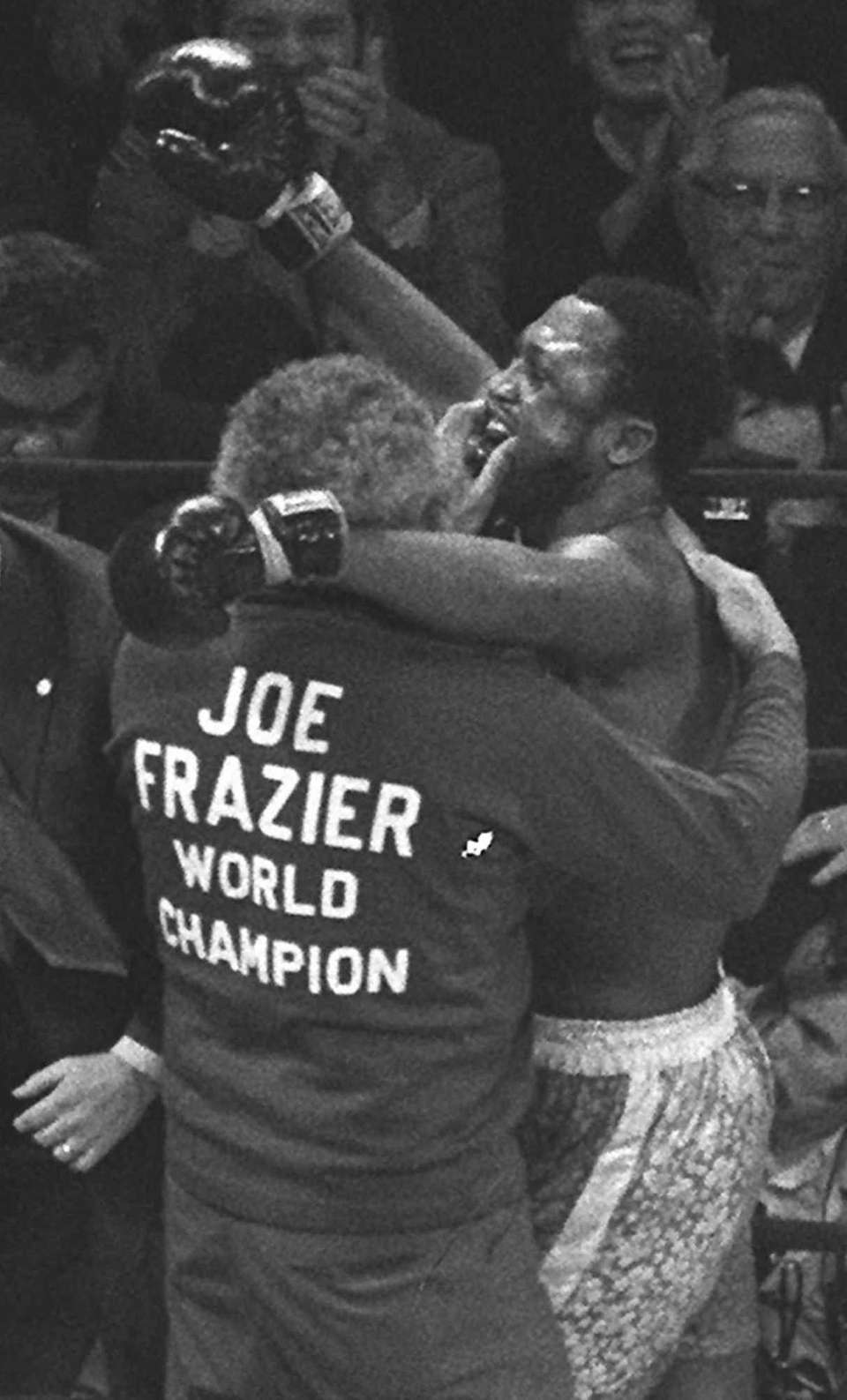 Joe Frazier, right, is hugged by his manager,