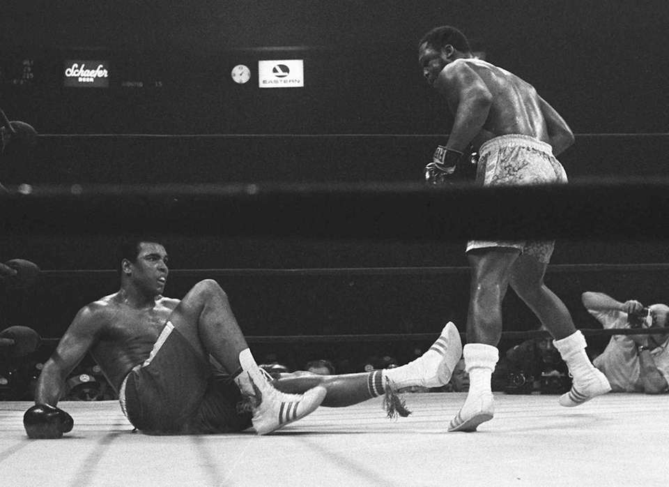 Joe Frazier stands over Muhammad Ali in the
