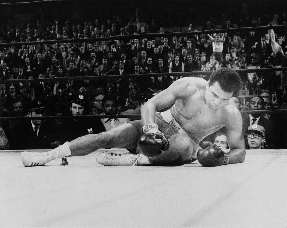 Boxer Muhammad Ali crouches on the canvas after