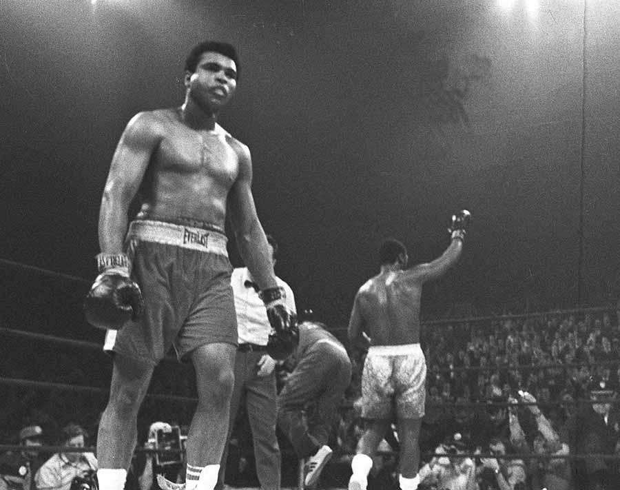 A battered Muhammad Ali walks back to his