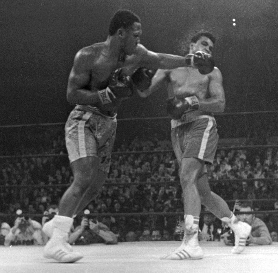 Muhammad Ali takes a left from Joe Frazier