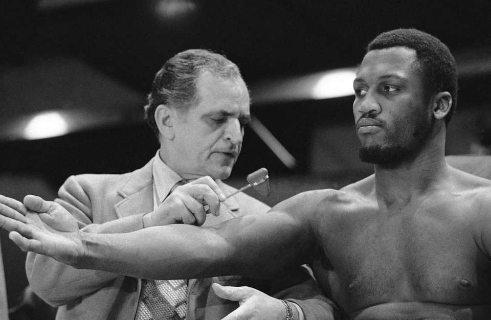 Title holder Joe Frazier extends his right army