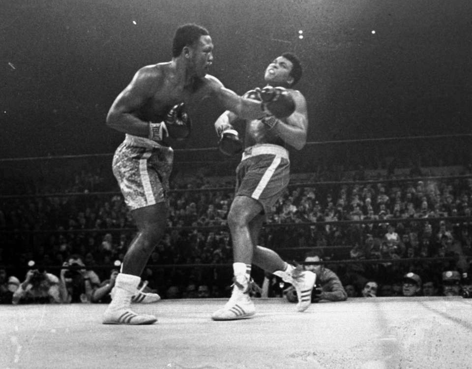 Joe Frazier, left, hits Muhammad Ali during the