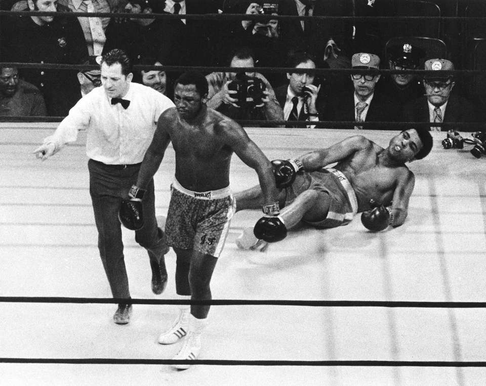 Boxer Joe Frazier being directed to the ropes