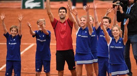 Novak Djokovic celebrates victory with the ballkids during