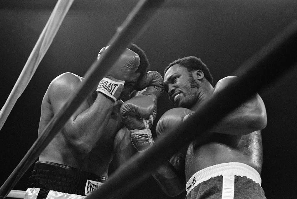 Muhammad Ali, left, brings his gloves to his