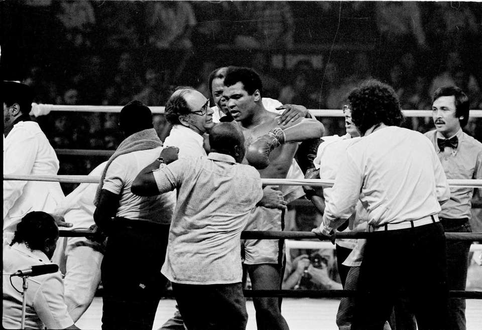 Muhammad Ali is in the ring surrounded by