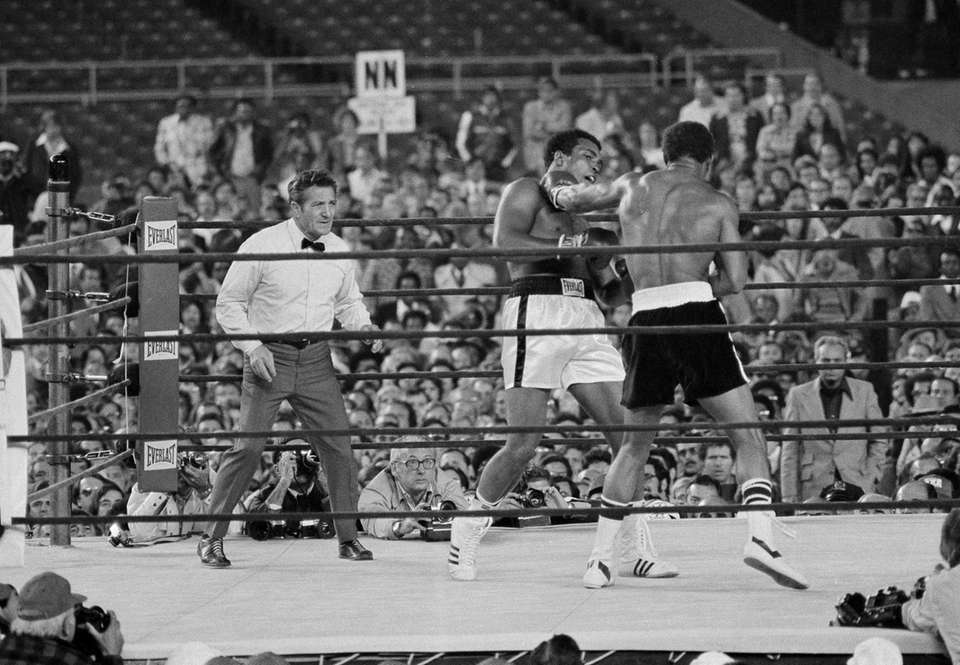 Heavyweight champion Muhammad Ali tries to avoid a