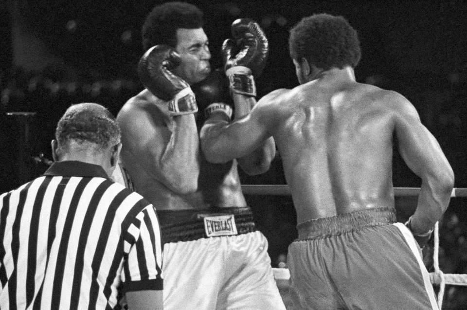 Muhammad Ali winces as he takes a George
