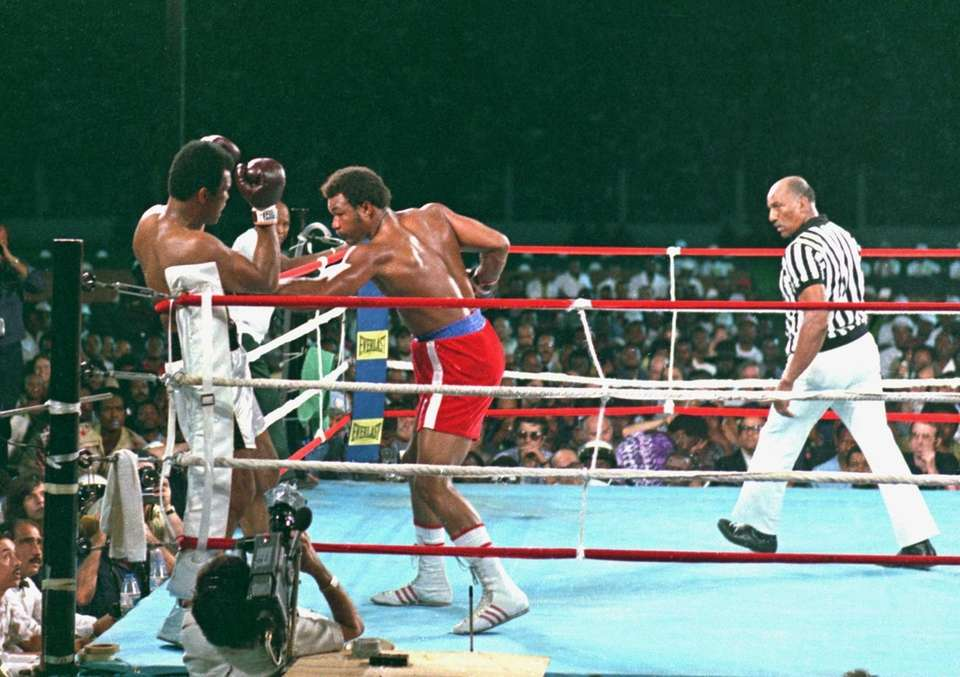 George Foreman, center, lands a body punch to