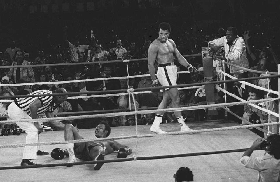 Referee Zack Clayton counts out George Foreman in