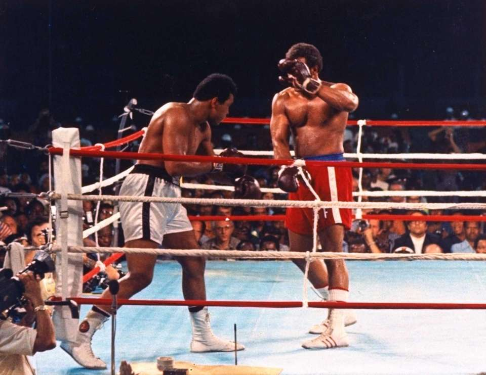 Champion George Foreman is shown covering up from