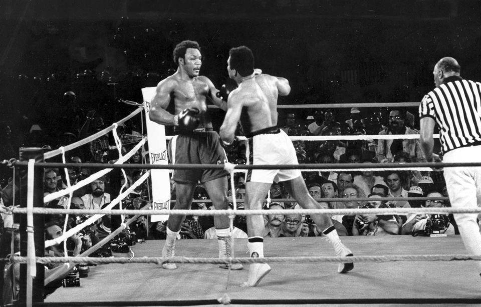 Defending world heavyweight champion George Foreman, left, watches