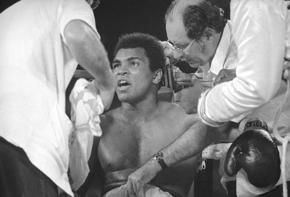 Muhammad Ali talks to his cornermen during his