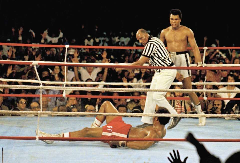 Muhammad Ali, right, stands back as referee Zack