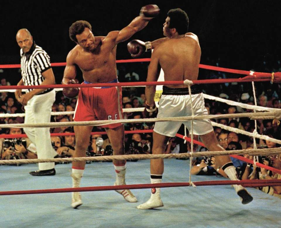 Muhammad Ali, right, deflects a punch by George