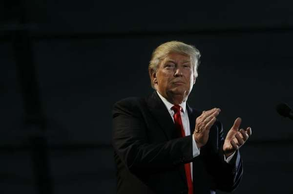 Republican presidential candidate Donald Trump applauds during a