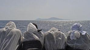 TOPSHOT - Migrants look at the Pantelleria island