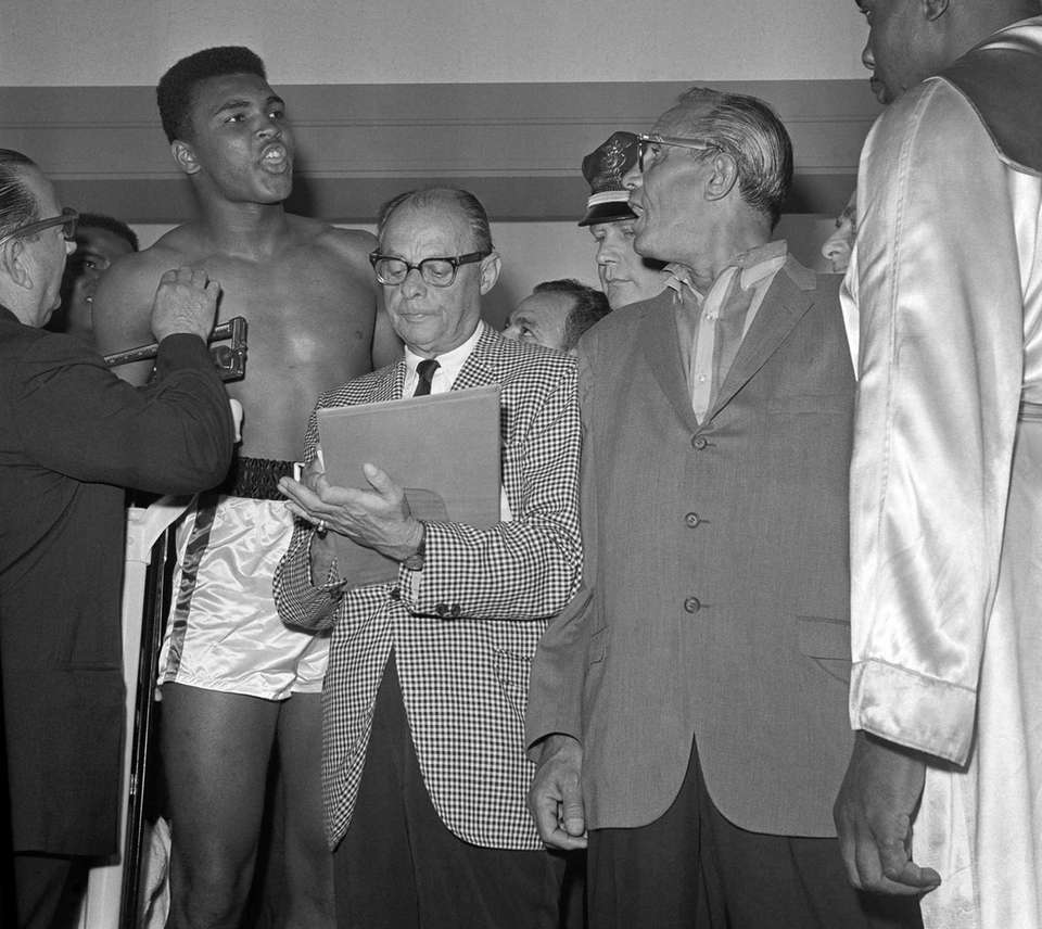 Cassius Clay, left, shouts as he stands on